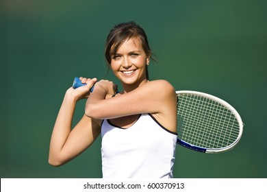 A pretty female tennis player smiles on court.