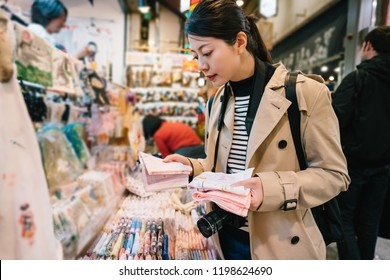pretty female traveler choosing handkerchief for her mom in the store. elegant traveler buying souvenir. Happy shopping in traditional specialty store in market in Japan.