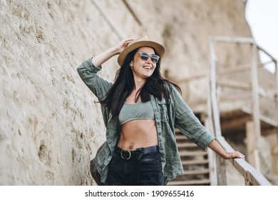 Pretty female traveler in hat and sunglasses with rocks behind