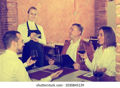 Pretty female waiter writing down order from visitors in country restaurant