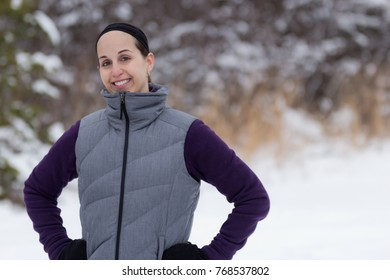 Pretty fit girl outside in winter smiles at camera
