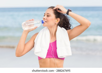 Pretty fit woman drinking water at the beach