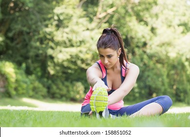 Pretty fit woman stretching sitting on the grass