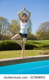 Pretty Fit Young Woman Doing Standing Balance Yoga Pose at the Poolside on a Sunny Morning.
