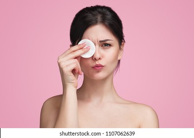 Pretty flawless model covering one eye with cotton pad looking at camera with pretty grimace on pink background