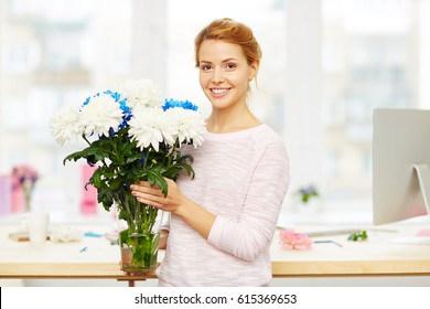 Pretty floral designer with messy hair bun at work: she standing in lovely studio and holding glass vase with white and blue chrysanthemums in hands