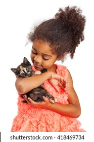 Pretty four year old multicultural girl holding and looking at a kitten