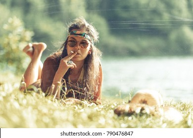 Pretty free hippie girl smoking on the grass. Peace. Body painting. Outdoor in peace and free love. Top view - Vintage effect photo