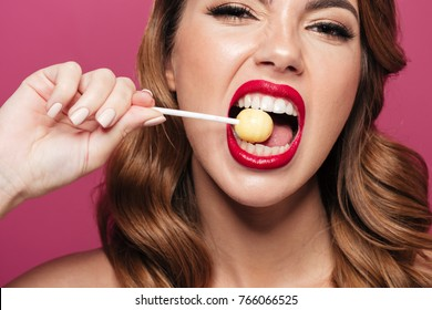 Pretty funny lady with make up and styling eating lollipop like watermelon isolated over pink