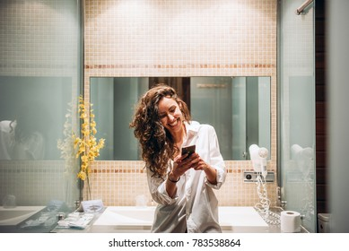 Pretty funny woman with mobile phone in the bathroom.