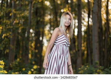 Pretty funny young blond woman in a stylish pink striped sundress walk on the forest among the trees on a bright sunny summer day. Cute joyful girl model resting in the park.