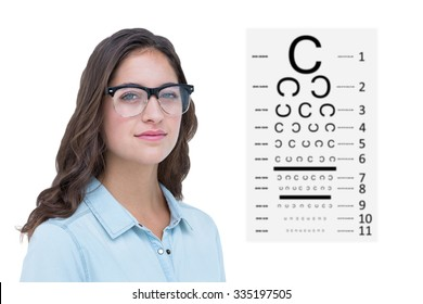Pretty geeky hipster looking at camera against eye test