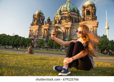 Pretty gil sitting in front of Berlin Cathedral at beautiful sunset and doing selfie