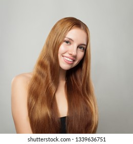 Pretty ginger haired woman with long healthy hair smiling on white background