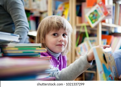 pretty  girl of 5 years old in library choosing books.