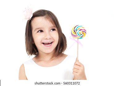 Pretty girl among the sweets, candies and lollipops. Funny child with candy lollipop, happy little girl eating big sugar lollipop, kid eat sweets. surprised child with candy.