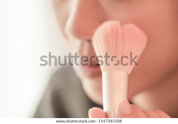 Pretty girl is applying blush on cheek by brush. Beauty Makeup.