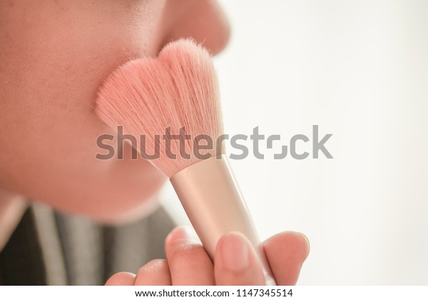 Pretty girl is applying blush on cheek by brush. Beauty Makeup.