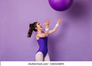 Pretty girl athlete in purple sports bodysuit in style of 80s throws fitball on isolated background