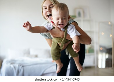 Pretty girl babysitting adorable toddler, having fun in stylish interior. Portrait of beautiful happy young Caucasian mom enjoying precious time with her cute baby son, holding him like flying plane