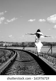 Pretty girl balancing on the railway