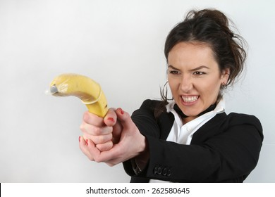 pretty girl and banana with condom - brunette in white shirt with a black jacket and black tie holding a banana with condom slipped - face expressions - Holds like shooting gun