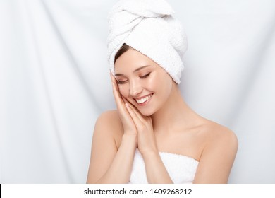 pretty girl in bath towel compose her arms near face and laughs with her eyes closed, happy woman after spa procedures