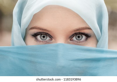 Pretty girl with beautiful big blue eyes, big eyelashes and eyebrows.  Portrait of beautiful woman with blue eyes wearing blue scarf