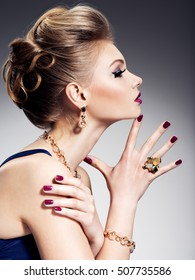 Pretty girl with beautiful hairstyle  and gold jewelry with bright make-up -  posing at studio