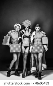 Pretty girl or beautiful woman in golden, carnival mask with feathers and sexy lingerie. Handsome, muscular men with muscle bodies in santa suits with Christmas presents on blue wall