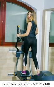 Pretty girl or beautiful woman in sportswear with fit, slim, sexy, body, exercises on cross trainer. Fitness gym workout
