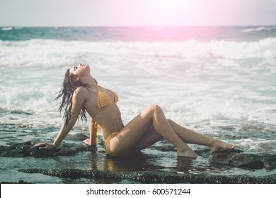 Pretty girl or beautiful woman with wet brunette hair, dirty with natural sand in sexy yellow swimsuit sitting on rocky beach on sunny summer day on blue sea background