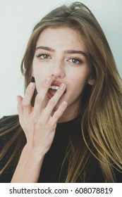 Pretty girl or beautiful woman with young face skin and long, blond hair, putting gel or balm on sexy lips on white wall. Cosmetology, beauty and spa