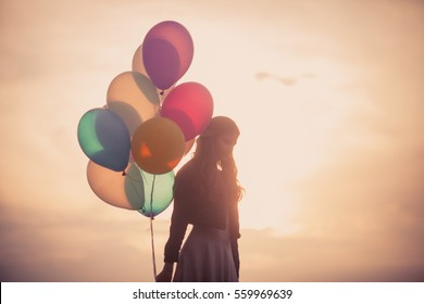 Pretty girl with big colorful balloons walking on the hills near the town. Focus on balloons