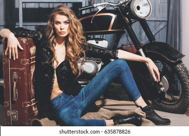 Pretty girl biker or cute woman with stylish, curly, long, blond hair and vintage suitcase in erotic black shirt and jeans sitting on garage floor at motorcycle. Traveling and active lifestyle
