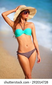 Pretty girl in a bikini on the beach. She enjoys while she walking on sand by the sea. She has a hat and sunglasses