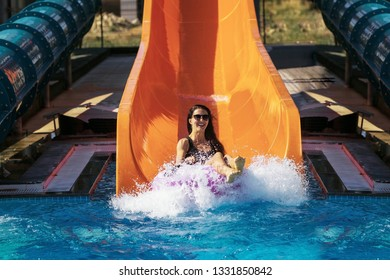 pretty girl in black bikini getting down on the inflatable ring by the slide in the aqua park. Summer Vacation. Enjoying suntan. Weekend on resort