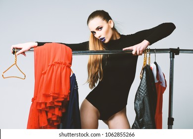 Pretty girl in black bodysuit hangs on clothes rack with dresses and hangers. Seduction and fashion concept. Girl with seductive face on grey background. Sexy woman with long hair and bright makeup