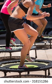 Pretty Girl with Black Top and Shorts Sportswear Having Exercise on Rebounder in Class at Gym