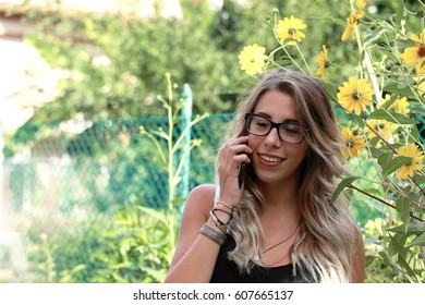 Pretty girl  with blonde hair talking on phone outside