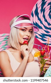 Pretty girl with blonde hair wearing top and pink cap standing with huge sweet lollypops at pink background, candy lover, drinking lemonade, close up portrait.