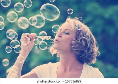 a pretty girl blowing bubbles - vintage toned