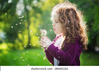 Pretty girl blowing dandelion. Background toning instagram filter.