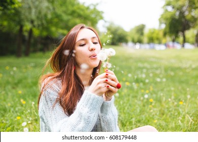 Pretty girl blowing dandelion in summer park. Green grass beautiful nature
