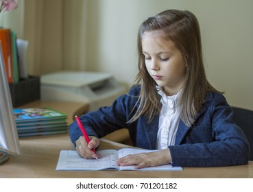 A pretty girl in a blue jacket and in a white blouse is sitting at the school desk.
