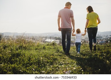 Pretty girl in blue jeans walks on a green hill holding hands of her parents