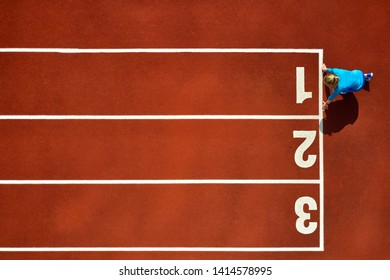 Pretty girl in a blue sportswear and sneakers is on start position on the running track number 1 at the stadium outdoors. Sun shines onto her body. Top view aerial photo. Horizontal.