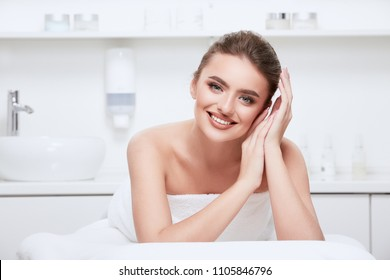 Pretty girl with brown hair fixed behind, clean fresh skin, big eyes and naked shoulders posing at spa cabinet background, wearing white towel and smiling, skin care concept.
