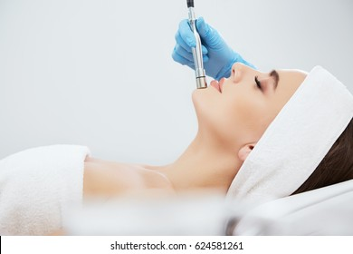 Pretty girl with brown hair fixed behind,clean fresh skin naked shoulders wearing white bath robe and hair wrap, doing cosmetic procedure at light medical background, portrait, microdermabrasion.