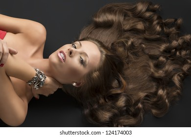 pretty girl with brown long curly hair lying on the black floor, she looks in to the lens and her left hand is on the neck